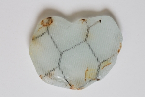 This unique piece is chicken wire embedded in textured striated glass (used for reinforcement and safety glass in cabinets, plus windows at schools and fire stations). This is a hot new vintage glass being recreated for current products. A piece of sea glass half this size was recently posted for sale on eBay with a starting bid of $69.99.