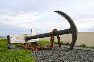 Anchor from shipwrecked American schooner Jamestown beside Kirkjuvogskirkja